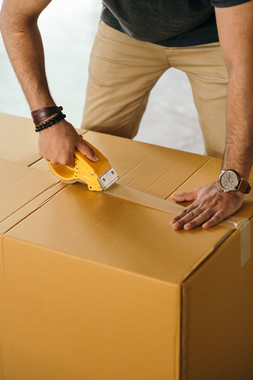 crop man sealing box with scotch tape